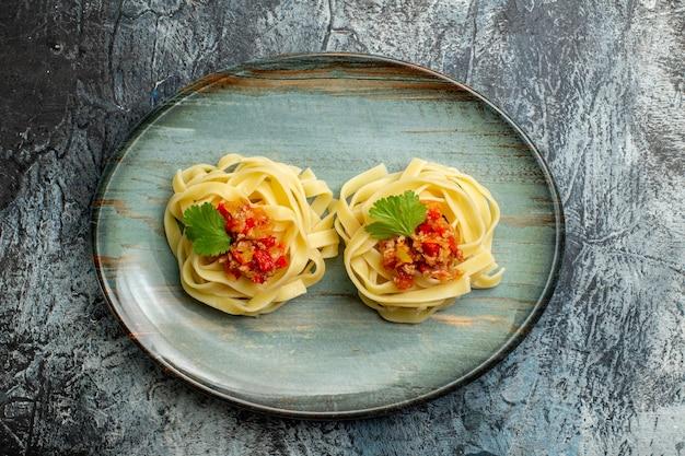 Bovenaanzicht van heerlijke pastamaaltijd met tomatenvlees en groen op een blauw bord op ijsachtergrond