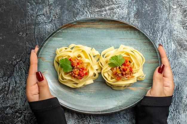 Bovenaanzicht van heerlijke pastamaaltijd op een blauw bord voor het diner op ijsachtergrond
