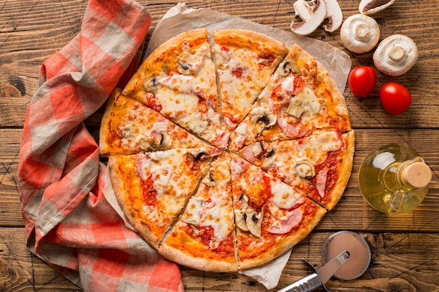 Bovenaanzicht van heerlijke pizza op houten tafel