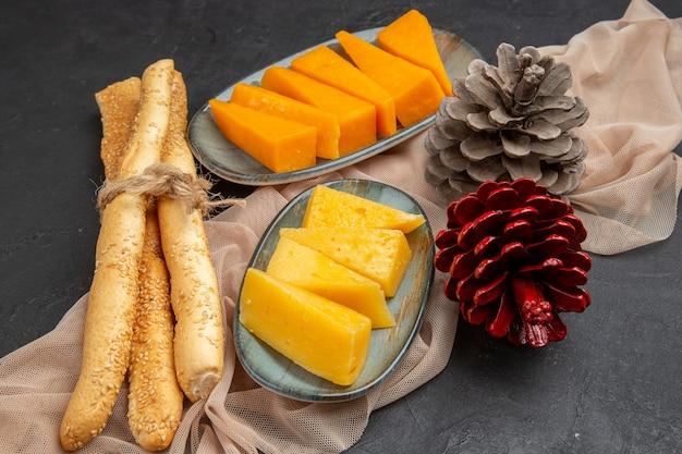 Bovenaanzicht van heerlijke plakjes kaas en coniferen op een handdoek op een zwarte achtergrond