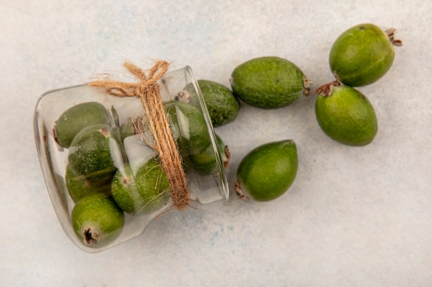 Bovenaanzicht van heerlijke rijpe feijoas die uit een glazen pot op een grijze ondergrond vallen