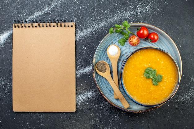 Bovenaanzicht van heerlijke rode linzensoep in een kom geserveerd met groene tomaten, peperzout op blauw dienblad en spiraalvormig notitieboekje op zwart witte achtergrond met vrije ruimte