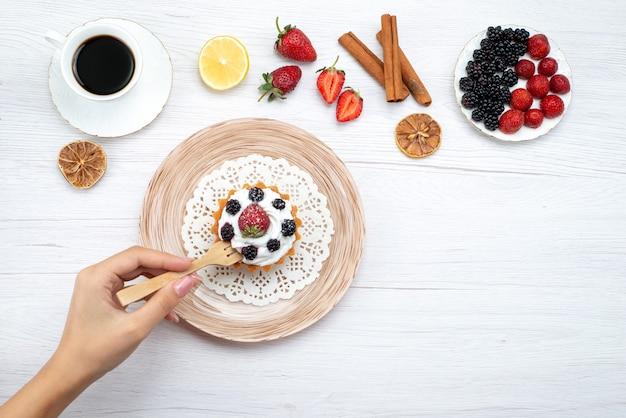 Bovenaanzicht van heerlijke romige cake met bessen eten krijgen door vrouw met kaneelkoffie op licht bureau, zoete cake