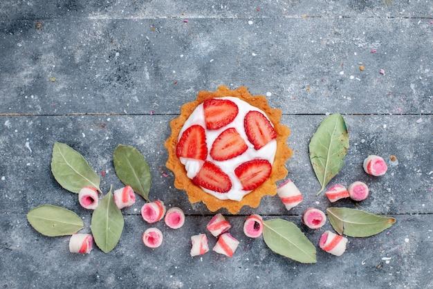 Bovenaanzicht van heerlijke romige cake met gesneden verse aardbeien en gesneden roze snoepjes op grijs, cake zoet bakroom fruit snoep