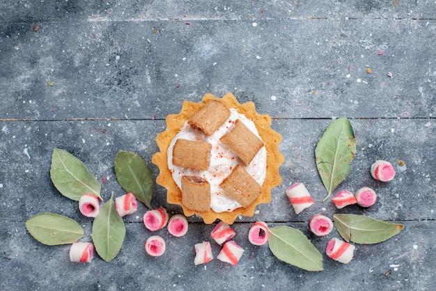 Bovenaanzicht van heerlijke romige cake met koekjes, samen met gesneden roze snoepjes op grijs, cake zoete bakroom