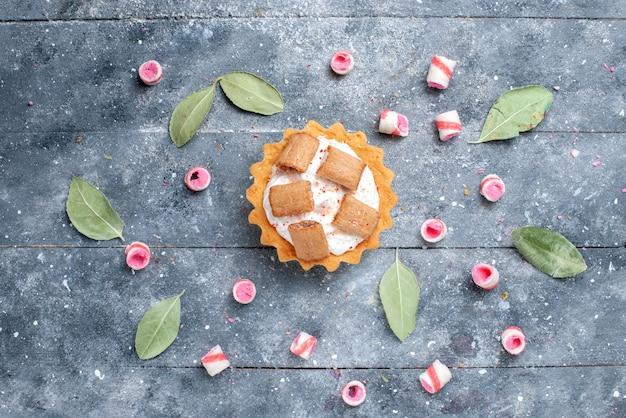Bovenaanzicht van heerlijke romige cake met koekjes, samen met gesneden snoepjes op grijs, zoete cake bakken suiker