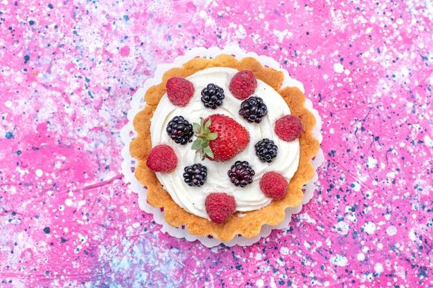Bovenaanzicht van heerlijke romige cake met verschillende bessen op paars helder, fruit bessen cake biscuit bak kleur