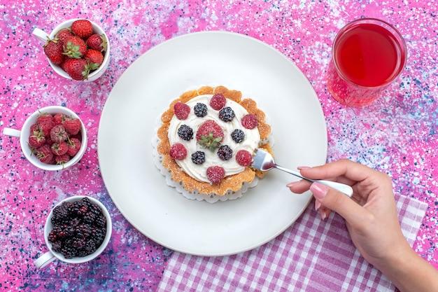 Bovenaanzicht van heerlijke romige cake met verschillende verse bessensap op helder licht bureau, bessenfruit vers zuur