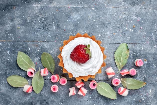 Bovenaanzicht van heerlijke romige cake met verse aardbeien en gesneden roze snoepjes op grijs, zoete cake bak room fruit snoep