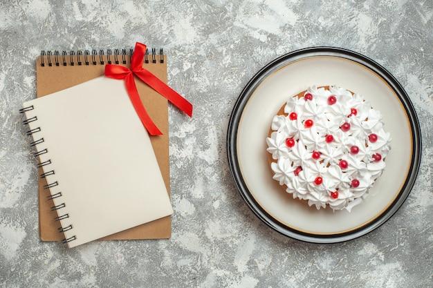 Bovenaanzicht van heerlijke romige cake versierd met fruit en notitieboekjes op ijsachtergrond