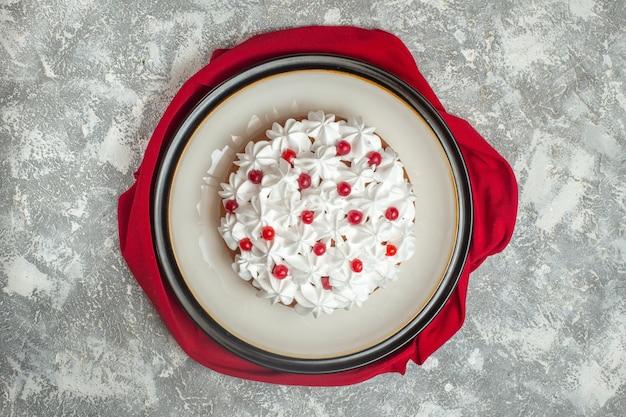 Bovenaanzicht van heerlijke romige cake versierd met fruit op een rode handdoek op ijsachtergrond
