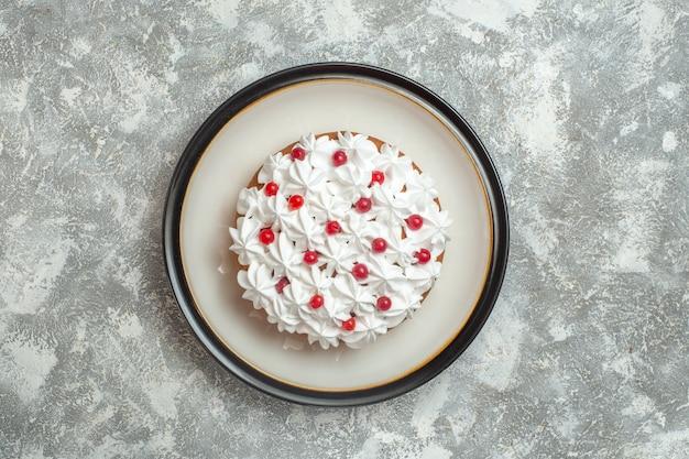Bovenaanzicht van heerlijke romige cake versierd met fruit op ijs achtergrond