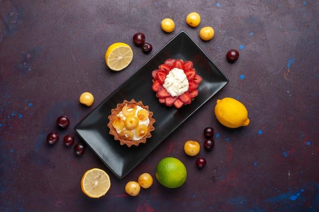 Bovenaanzicht van heerlijke romige taarten in plaat met citroenen en fruit op donkere ondergrond