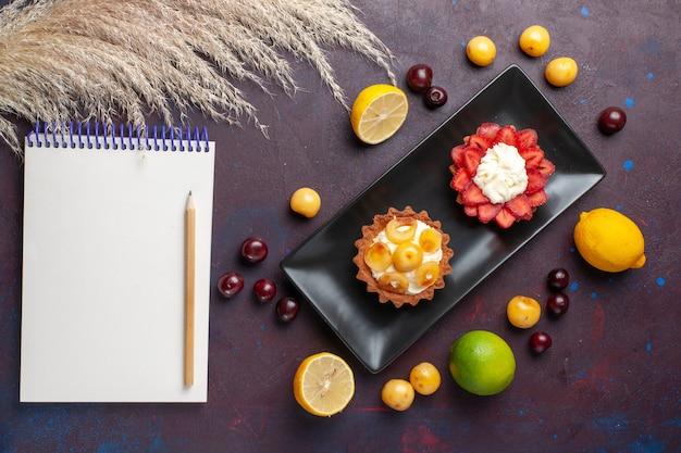 Bovenaanzicht van heerlijke romige taarten in plaat met verse citroenen en fruit op het donkere oppervlak
