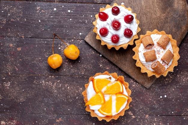 Bovenaanzicht van heerlijke romige taarten met gesneden fruit op bruin houten, cake biscuit fruit zoet bakken