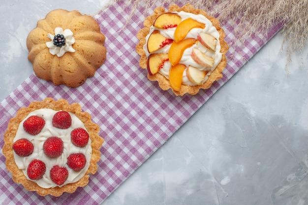 Bovenaanzicht van heerlijke romige taarten met gesneden fruit op licht bureau, cake biscuit zoete room bak thee suiker