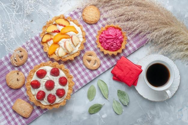 Bovenaanzicht van heerlijke romige taarten met gesneden fruit samen met koekjes en thee op licht bureau, cake biscuit zoete room bakken