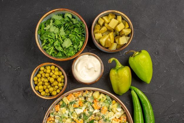 Bovenaanzicht van heerlijke salade met ingrediënten op donkere ondergrond