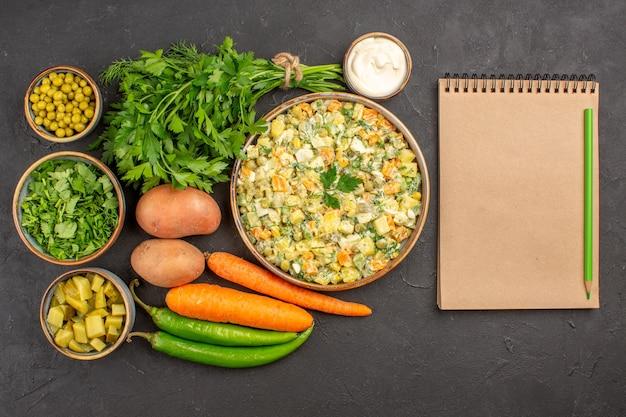 Bovenaanzicht van heerlijke salade met verse groenten op donkere ondergrond
