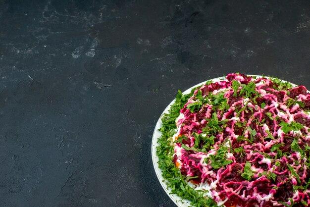 Bovenaanzicht van heerlijke salade versierd met groen in een witte plaat aan de linkerkant op zwarte achtergrond met vrije ruimte