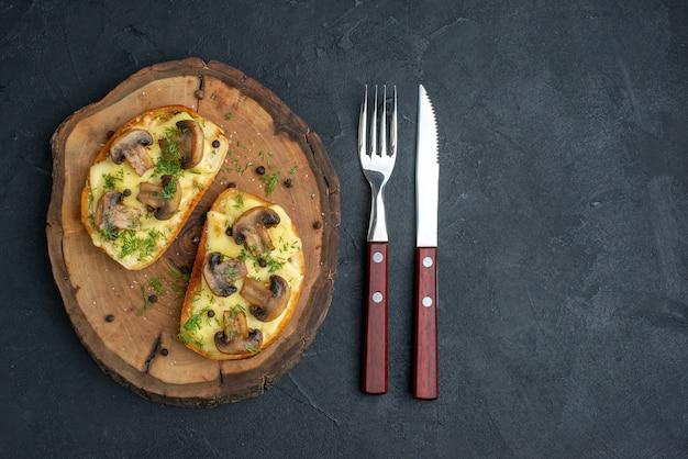 Bovenaanzicht van heerlijke snack met champignons op een houten bord en bestek op zwarte achtergrond met vrije ruimte