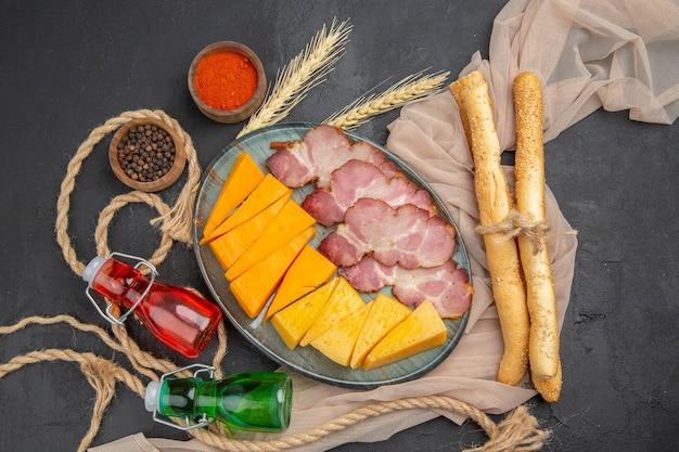 Bovenaanzicht van heerlijke snacks gevallen flessen pepers op handdoek en touw op een zwarte achtergrond