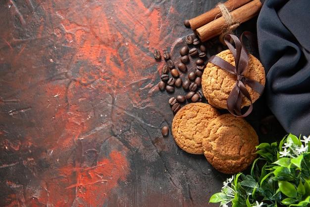 Bovenaanzicht van heerlijke suikerkoekjes en koffiebonen bloempot kaneel limoenen handdoek aan de linkerkant op donkere mix kleuren achtergrond