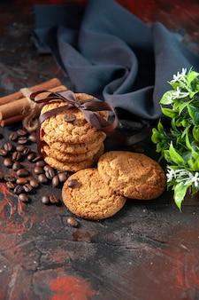 Bovenaanzicht van heerlijke suikerkoekjes en koffiebonen bloempot kaneel limoenen handdoek op donkere mix kleuren achtergrond