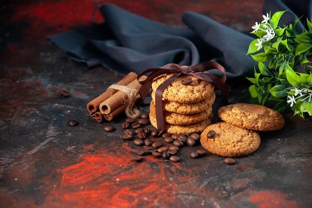 Bovenaanzicht van heerlijke suikerkoekjes en koffiebonen bloempot kaneel limoenen op donkere mix kleuren achtergrond