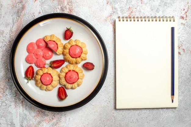Bovenaanzicht van heerlijke suikerkoekjes met aardbeigelei op een wit oppervlak