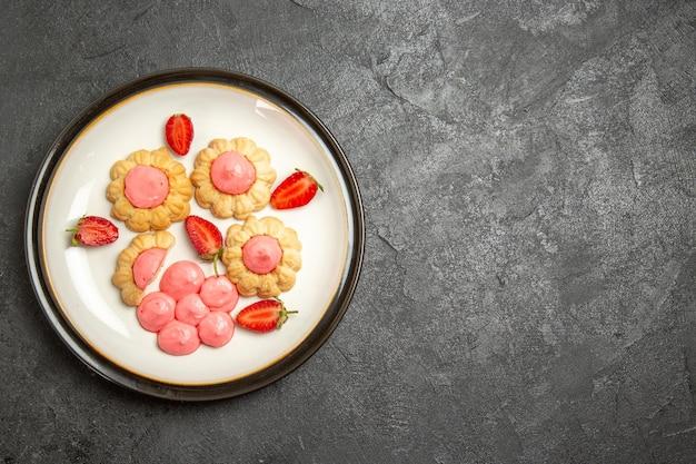 Bovenaanzicht van heerlijke suikerkoekjes met aardbeigelei op grijze ondergrond