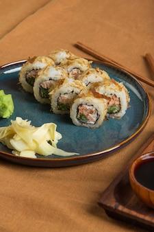 Bovenaanzicht van heerlijke sushi rollen met ingrediënten op houten tafel