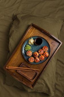 Bovenaanzicht van heerlijke sushibroodjes met ingrediënten in bed