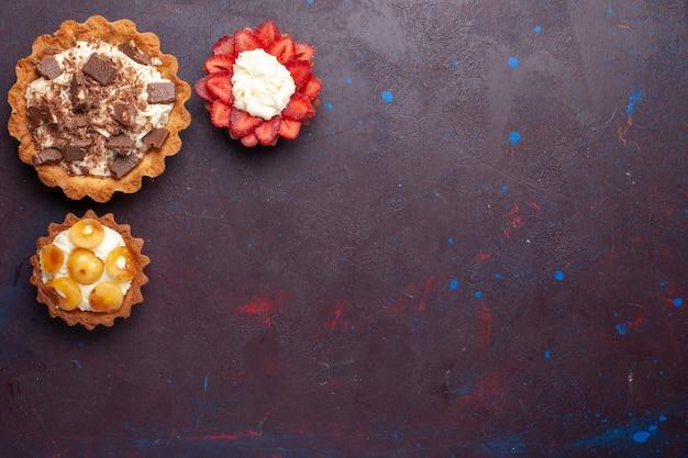 Bovenaanzicht van heerlijke taarten met room en chocolade op een donkere ondergrond