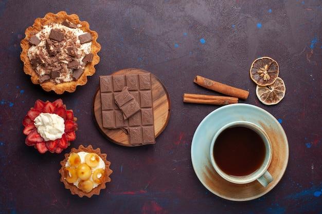 Bovenaanzicht van heerlijke taarten met roomchocolade en fruit, samen met thee op het donkere oppervlak
