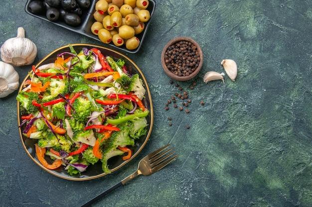 Bovenaanzicht van heerlijke veganistische salade in een bord met verschillende groenten en vork peper groene zwarte olijven knoflook aan de rechterkant op donkere achtergrond