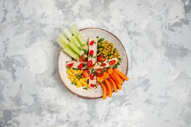 Bovenaanzicht van heerlijke veganistische salade op een bord op een witte ondergrond met vrije ruimte