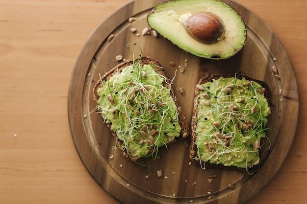 Bovenaanzicht van heerlijke veganistische sandwich met guacamole en microgreens bovenop. de helft van avocado met sandwich op houten bord. veganistisch eten concept.