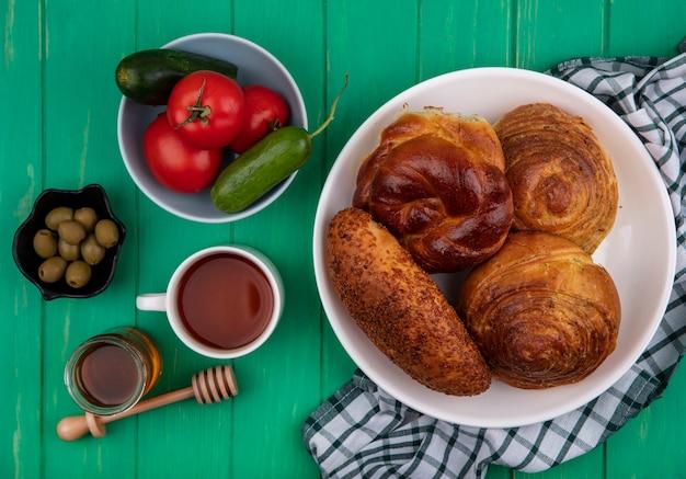 Bovenaanzicht van heerlijke verse broodjes op een witte plaat op een gecontroleerde doek met groenten op een kom met honing op een glazen pot op een groene houten achtergrond