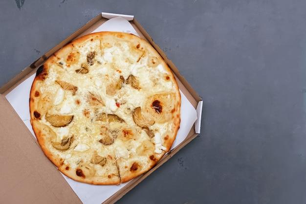 Bovenaanzicht van heerlijke vier kaas pizza in kartonnen doos