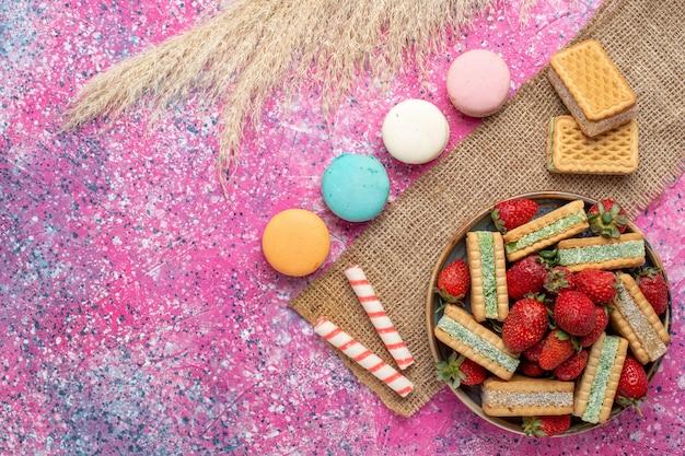 Bovenaanzicht van heerlijke wafelkoekjes met franse macarons op roze oppervlak