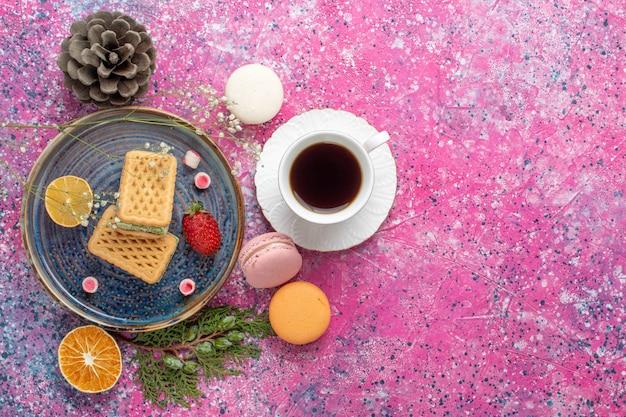 Bovenaanzicht van heerlijke wafels met franse macarons en thee op het roze oppervlak