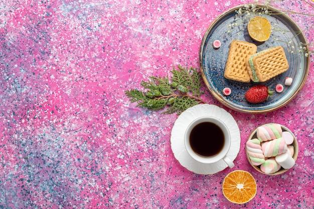 Bovenaanzicht van heerlijke wafels met kopje thee en marshmallows op roze ondergrond