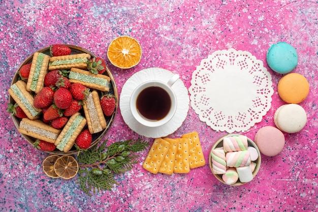Bovenaanzicht van heerlijke wafels met kopje thee en verse rode aardbeien op het roze oppervlak
