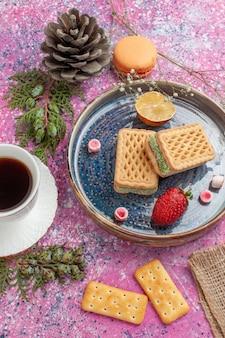 Bovenaanzicht van heerlijke wafels met kopje thee op roze bureau