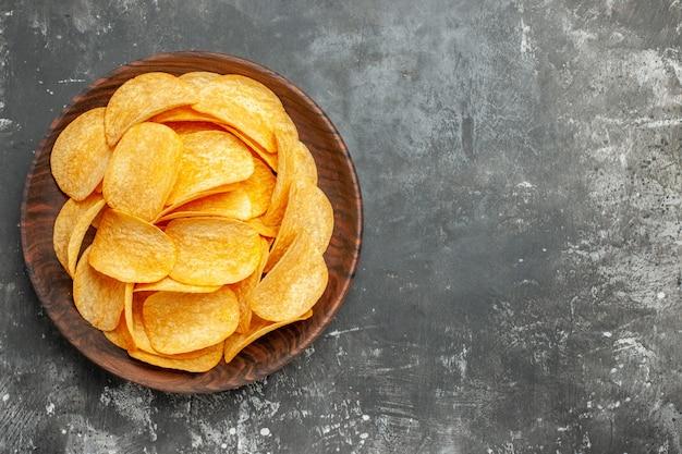 Bovenaanzicht van heerlijke zelfgemaakte aardappelchips op een bruine plaat op grijze achtergrond