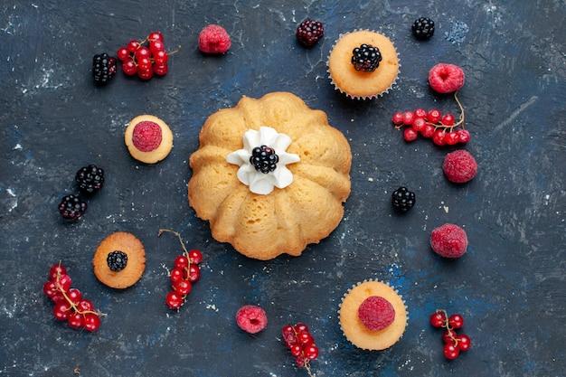 Bovenaanzicht van heerlijke zoete cake met verschillende bessen en lekkere room samen met veenbessen verspreid op een donker bureau, zoete fruitbessentaart