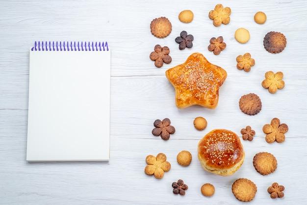 Bovenaanzicht van heerlijke zoete gebakjes met koekjes en blocnote op licht bureau, gebak cookie koekje zoete suiker