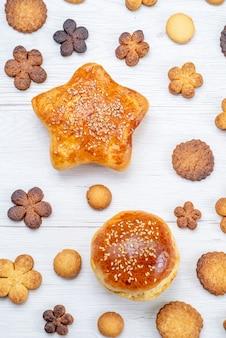 Bovenaanzicht van heerlijke zoete gebakjes met lekkere koekjes op licht, gebak cookie koekje zoete suiker