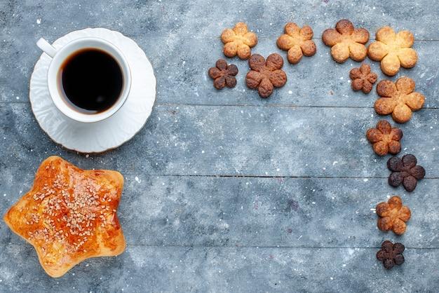 Bovenaanzicht van heerlijke zoete gebakjestervormige met koekjeskoffie op grijs, zoete bak gebakjecake